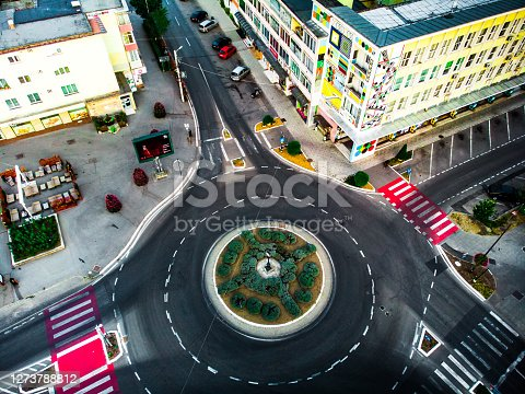 High angle topdown image, taken by drone, of a car driving round a roundabout in the city.