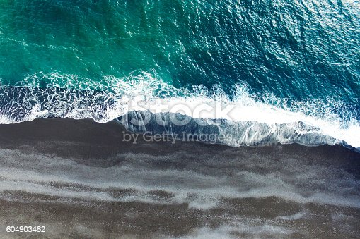 Cold ocean waves washing down the black sand beach making a lot of ocean foam. The video is taken by drone which goes down to 350 meters and rotates.