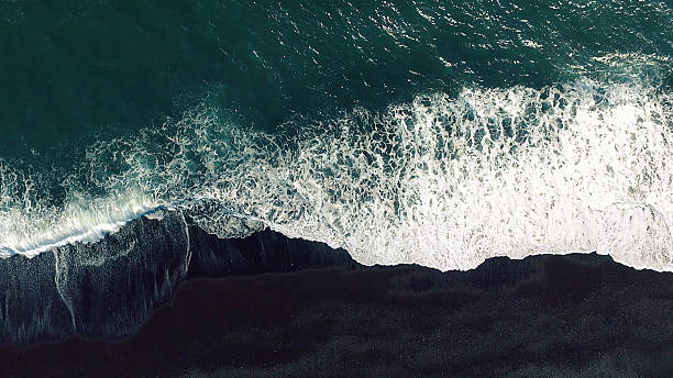 Aerial tracking shot Cold ocean waves washing down the black sand beach making a lot of ocean foam. The video is taken by drone which goes down to 350 meters and rotates. 4k resolution stock pictures, royalty-free photos & images