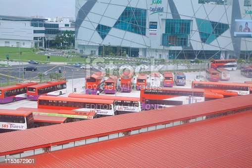 Aerial vie of bus terminal in Singapore Kallang from skytrain. In background is modern building. Many buses are parked.