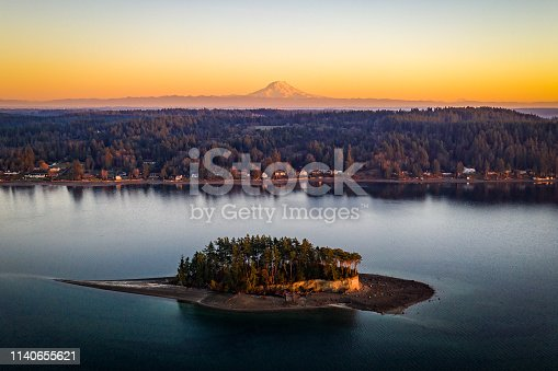 An aerial view of Cutts Island with Mt Rainier in the background at golden hour Puget Sound Washington