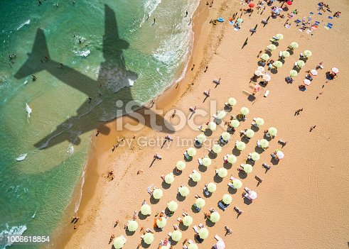 istock Aerial view airplane shadow and beach with umbrellas 1006618854