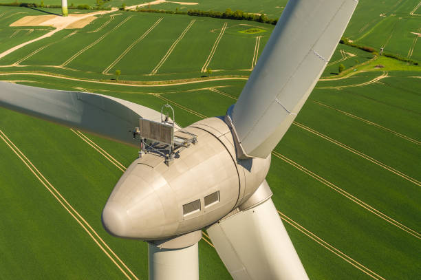 Aerial view and closeup of a wind turbine in a wind farm windmill sustainable windmill stock pictures, royalty-free photos & images