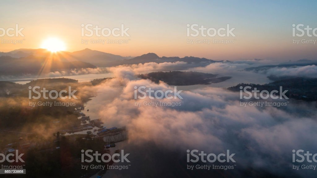 Aerial view and morning mist top view at Mon Bridge in sangkhlaburi,Kanchanaburi,Thailand. It is a popular place for tourists. Images may be blurry due to fog. stock photo