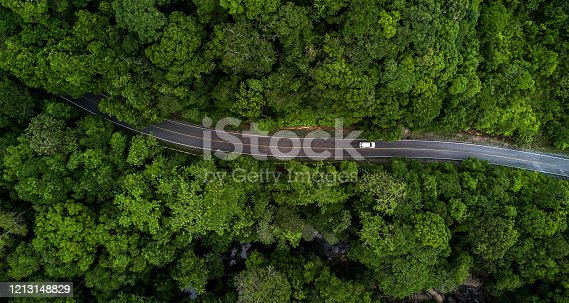 istock Aerial view asphalt road and green forest, Forest road going through forest with car adventure view from above, Ecosystem and ecology healthy environment concepts and background. 1213148829