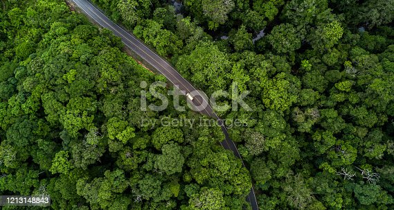 1042711480 istock photo Aerial view asphalt road and green forest, Forest road going through forest with car adventure view from above, Ecosystem and ecology healthy environment concepts and background. 1213148843