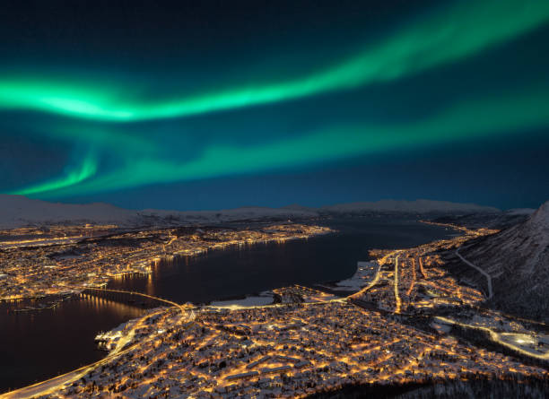 Aerial view at night from Storsteinen hill on Tromso city with beautiful shapes of aurora borealis stock photo