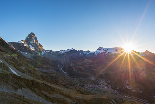 Aerial view at sunrise of Breuil Cervinia village  and Cervino or Matterhorn mountain peak, famous ski resort in Aosta Valley, Italy.