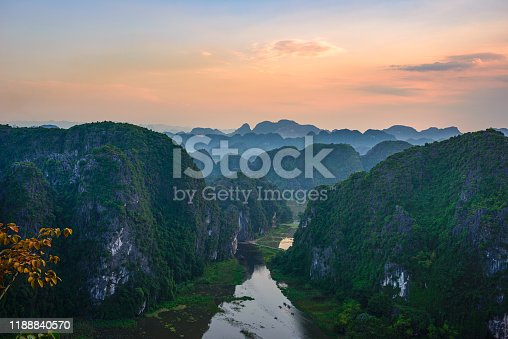 Aerial view at sunset of Ninh Binh region, Tam Coc valley tourist attraction, UNESCO World Heritage Site, scenic river crawling through karst mountain ranges in Vietnam, travel destination.