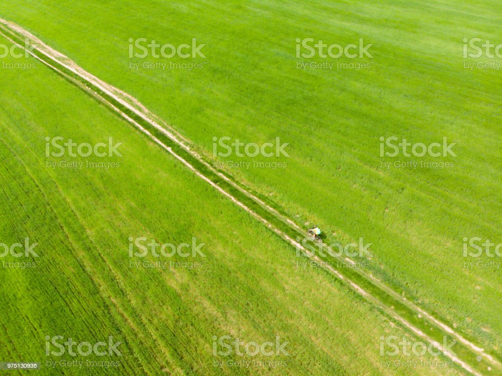 aerial view. bicyclist riding green field. trail road stock photo