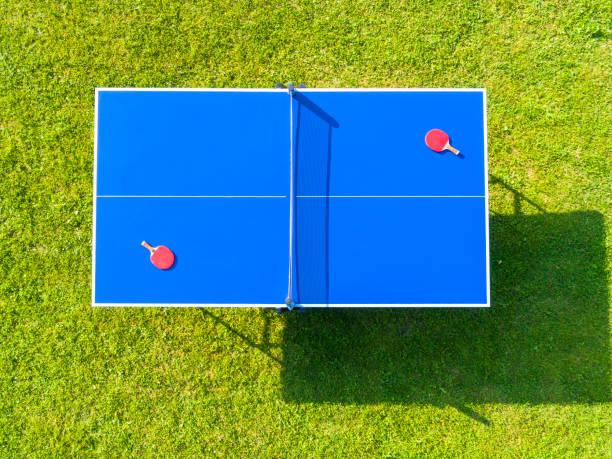 Luftbild blaue Tischtennis oder Tischtennis. Nahaufnahme Ping-Pong Netz. Schließen Sie Ping-Pong-Netz und Linie. Ansicht von oben zwei Tischtennis- oder Tischtennisschläger oder Paddel und Ball auf einem blauen Tisch mit Netz – Foto