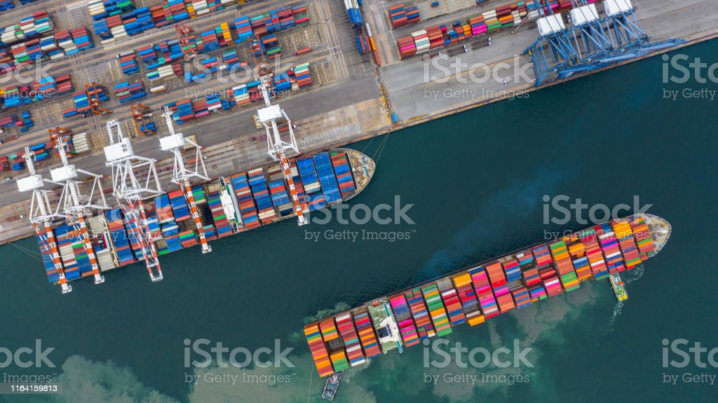 Aerial view cargo ship terminal, Unloading crane of cargo ship terminal, Aerial view industrial port with containers and container ship. Aerial view cargo ship terminal, Unloading crane of cargo ship terminal, Aerial view industrial port with containers and container ship. Aerial View Stock Photo