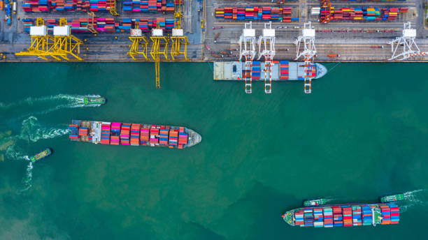 Aerial view cargo ship terminal, Unloading crane of cargo ship terminal, Aerial view industrial port with containers and container ship. stock photo