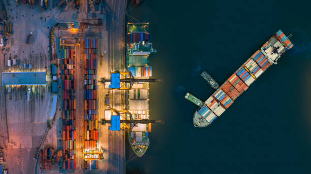 aerial view container ship from sea port working for delivery containers shipment. suitable use for transport or import export to global logistics concept. - drone shipyard night imagens e fotografias de stock