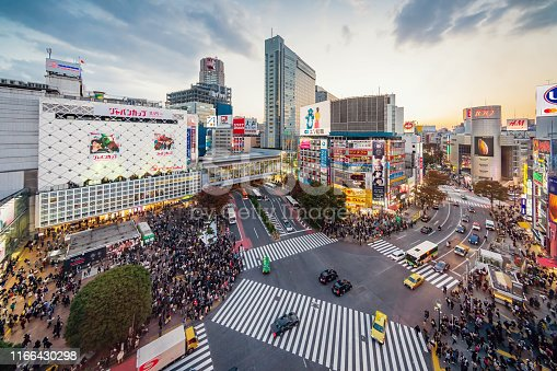 Aerial View of people waiting at the crowded crossing at Shibuya Crossing in Downtown Tokyo, illuminated Shibuya Buildings with billboards in the background. Twilight light, close to sunset. Shibuya Crossing, Shibuya Ward, Tokyo, Japan, Asia.