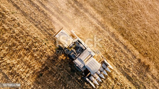 1072634078 istock photo Aerial view, details of farmer using combine to harvest crops 1075904756