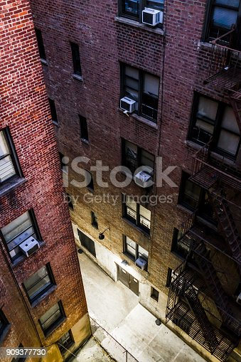 Aerial view down of illuminated brick apartment condo building architecture in Fordham Heights center, Bronx, NYC, Manhattan, New York City with fire escapes, windows, ac units in morning, evening, night