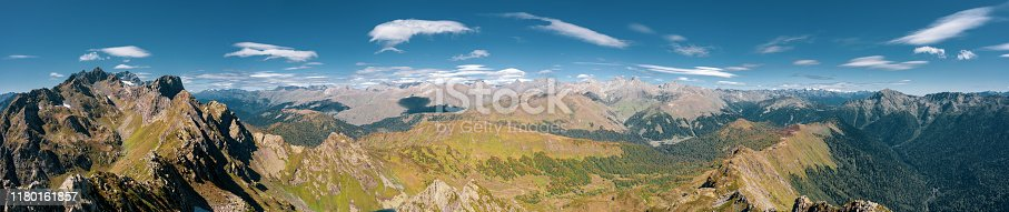 Aerial drone wide panoramic view of Caucasus mountains; rocky steep slopes, alpine meadows and snow fields; wild autumn nature, mixed forest and scenic skyline; place for hiking, tracking and tourism