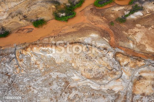 Aerial view; drone flying forward over a polluted river with destroyed ecosystem and copper tailing dump poisoning ground and water; air emissions from industry; environmental disaster in South Ural