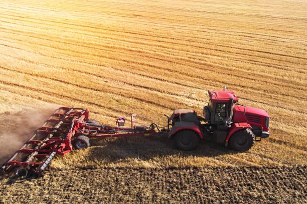 Luftbild-Drohne von erntefeld mit Traktor mäht Trockenrasen. Im Herbst gelbes Feld mit einem Heuhaufen nach Ernte Draufsicht. Ernte in den Bereichen. Vorrat an Heu für den Winter. Ansicht von oben. – Foto