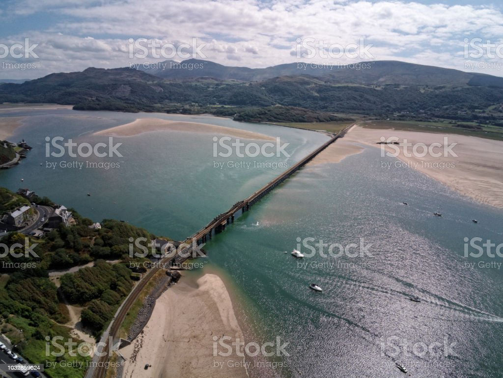 Aerial view, Drone panorama over rising tide sea, bay, anchored boats, steel railway bridge in Barmouth, Wales stock photo