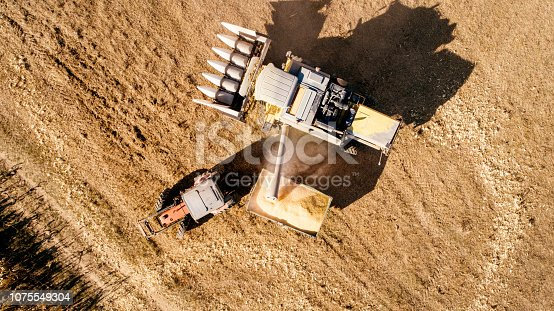 1072634078 istock photo Aerial view, drone view of combine harvester working the fields. 1075549304