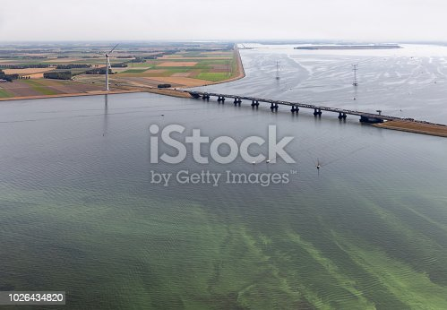 istock Aerial view Dutch landscape with bridge, wind turbine and algae 1026434820