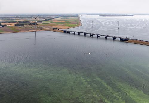 istock Aerial view Dutch landscape with bridge, wind turbine and algae 1026434820
