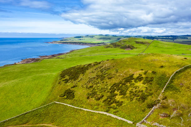 Aerial view from a drone of agricultural land next to the coast in rural Dumfries and Galloway, south west Scotland High angle view from a drone of farmland next to the coast in rural Dumfries and Galloway, Scotland. The land is mainly used to graze livestock. johnfscott stock pictures, royalty-free photos & images