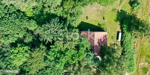 Aerial view from a vertical perspective of a small shed at the edge of a forest with a meadow in front of it.