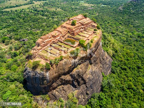 Aerial view from above of Sigiriya or the Lion Rock, an ancient fortress and a palace with gardens, pools, and terraces atop of granite rock in Dambulla, Sri Lanka. Surrounding jungles and landscape.