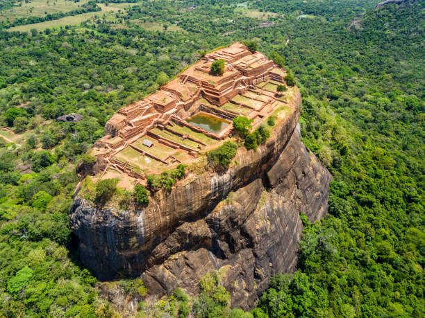 aerial view from above of sigiriya or the lion rock, an ancient fortress and a palace with gardens, pools, and terraces atop of granite rock in dambulla, sri lanka. surrounding jungles and landscape - unesco foto e immagini stock