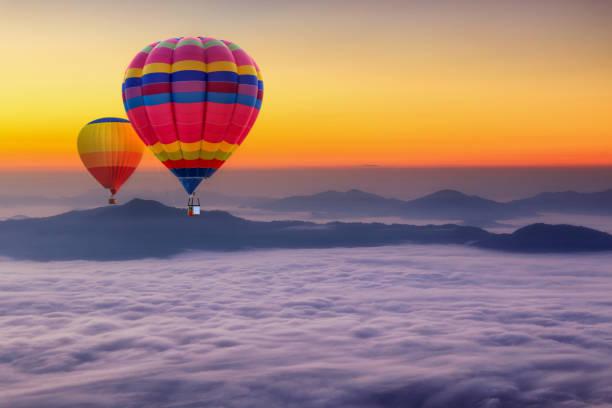 vue aérienne de montgolfières coloré survolant avec la brume au mont pha tung dans la durée de l'aube, province de chiang rai, thaïlande - montgolfière photos et images de collection