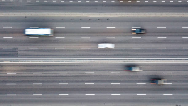 Aerial view from the drone directly above the road to the high-speed highway with high-speed cars. stock photo