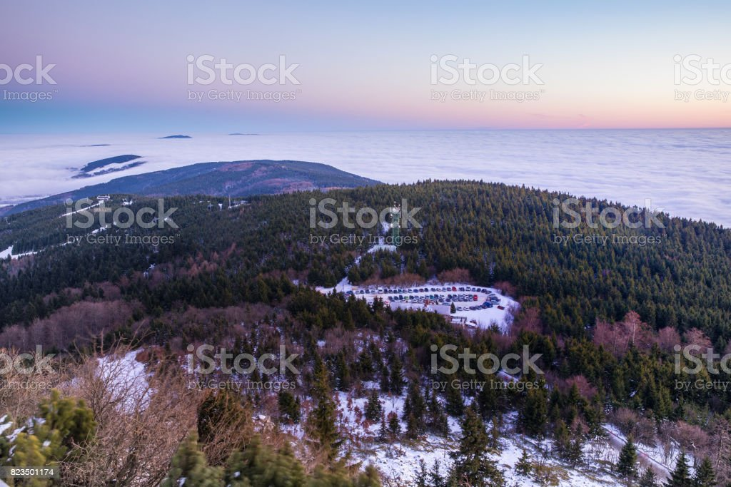 Aerial view from the tower Jested hill to the parking lot below. Inverno valley bathed in fog. Beautifully colored sky after sunset. Cyech Republic stock photo