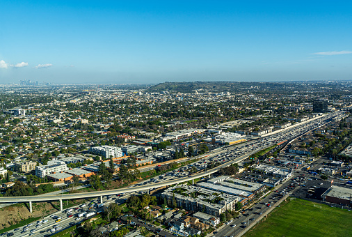 Aerial View high above the 405 Freeway in Los Angeles looking south east with Palms and Culver City in the background