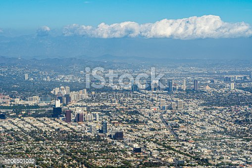 Aerial View high above West Los Angeles looking at Miracle Mile, Century City, down Olympic Boulevard with clouds in the background above east LA.