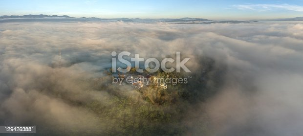 istock Aerial view in the morning with sea of fog at The iconic standing Buddha on Wat Phra That Khao Noi one of the most tourist attraction places in Nan province of northern Thailand during the sunrise 1294263881