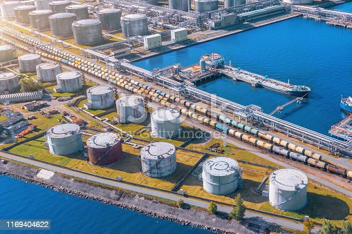 Aerial view large port oil loading terminal with large storage tanks. Railway infrastructure for the delivery of bulk cargo by sea, using pump station in ship tanker for transportation and delivery