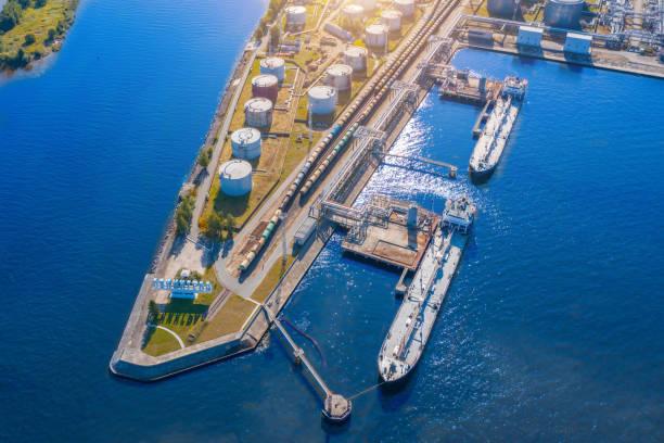 luchtfoto grote haven olie laad terminal met grote opslagtanks. spoorweginfrastructuur voor de levering van bulkgoederen over zee - brandstoftank stockfoto's en -beelden