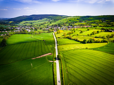 Aerial view looking down on a rural road in the UK countryside with a car racing along it.
