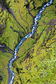 A blue mountain stream flowing between two rocky green hills. Aerial drone photo taken in Iceland.