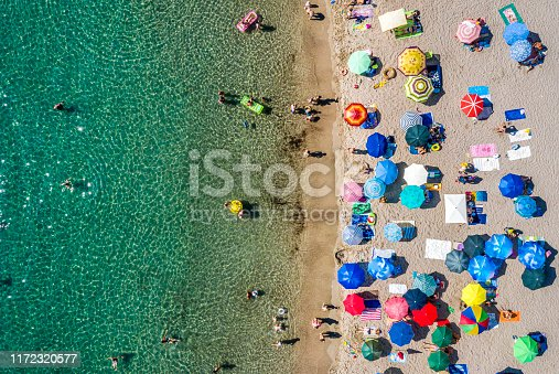 Drone view of a beach coastline of a dirty jade-colored water. Sunbeds and umbrellas are on the beach.