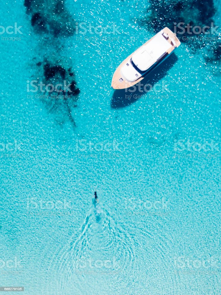 Aerial view of a boat in front of the Mortorio island in Sardinia. Amazing beach with a turquoise and transparent sea. Emerald Coast, Sardinia, Italy. - foto stock