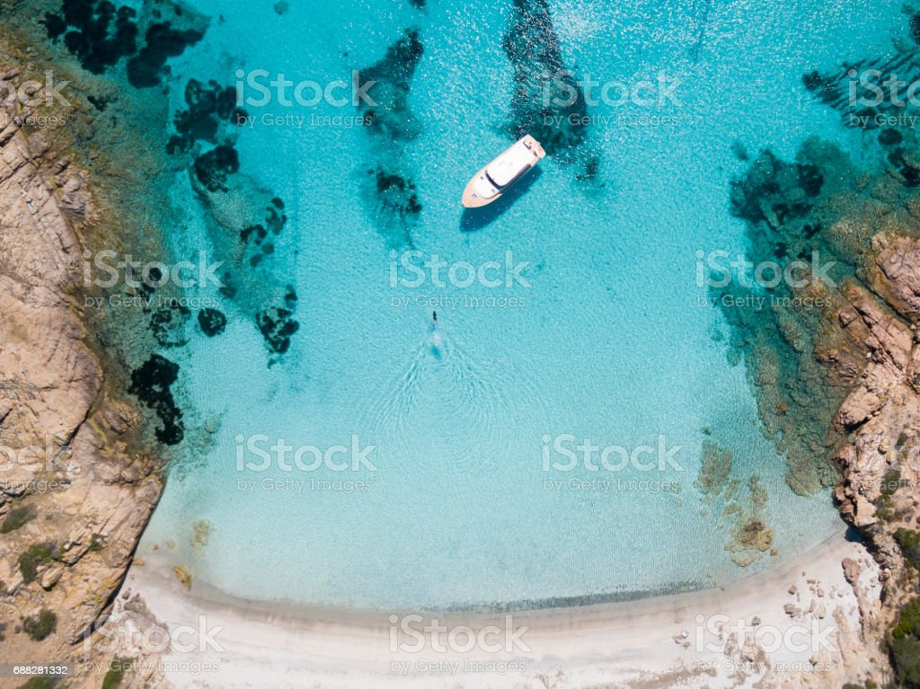 Aerial view of a boat in front of the Mortorio island in Sardinia. Amazing beach with a turquoise and transparent sea. Emerald Coast, Sardinia, Italy. stock photo