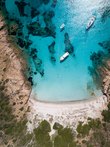 aerial view of a boat in front of the mortorio island in sardinia. amazing beach with a turquoise and transparent sea. emerald coast, sardinia, italy. - sardegna foto e immagini stock