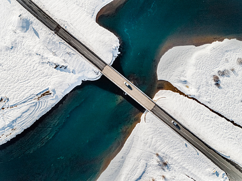 Aerial view of a bridge connecting two roads over a river