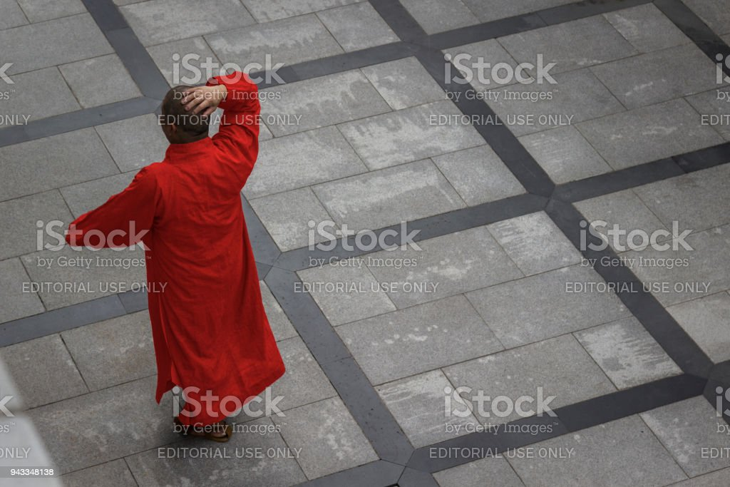 Aerial view of a buddhist monk dressed in an orange robe, walking along the pavement. stock photo