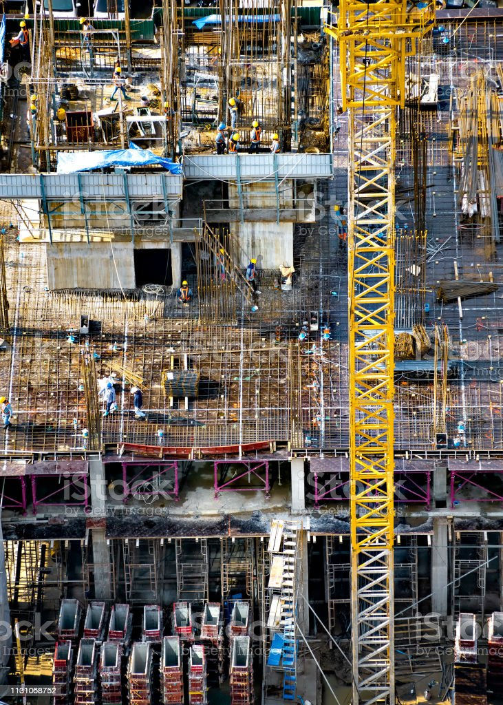 Aerial view of a building construction site in progress with tower...