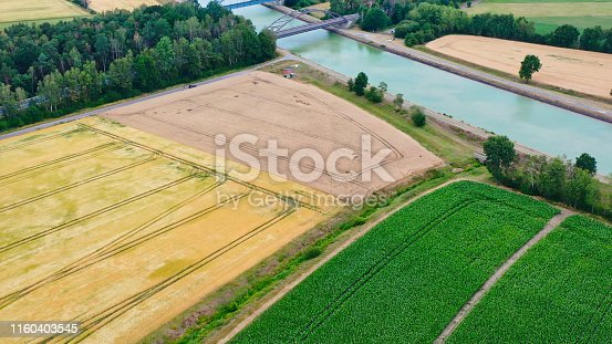Aerial view of a canal that runs through fields, meadows and arable land in the flat landscape of northern Germany.